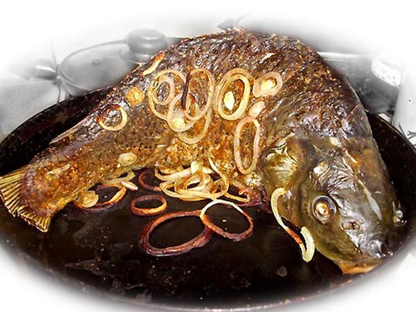 Постная запеченная рыба с украшением колечками лука.
